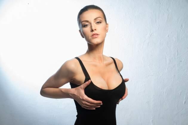 Žena ukazuje prsia