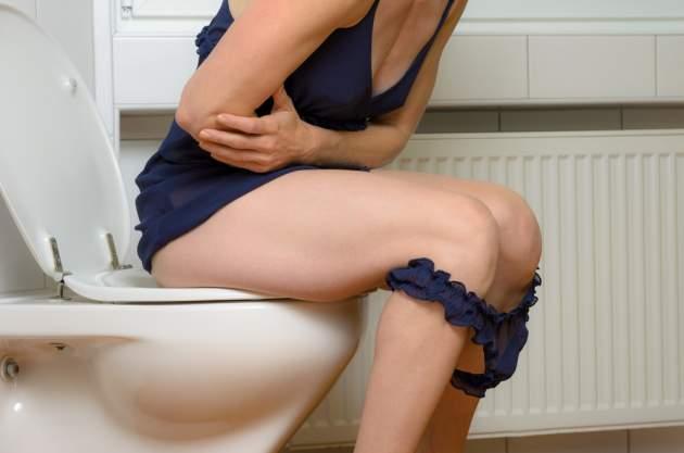Žena s bolesťami na toalete
