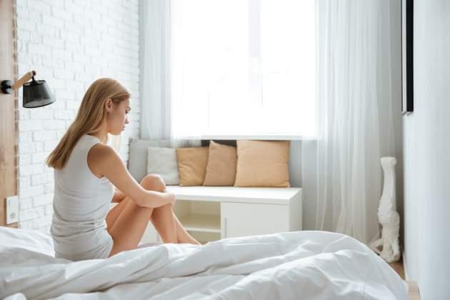 Smutná žena na posteli