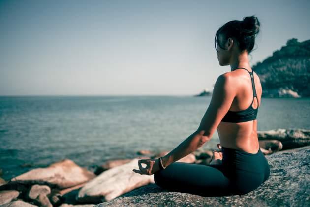 Žena medituje pri vode